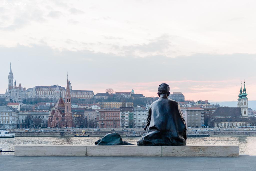 Возле здания парламента памятник поэту печально смотрит на Дунай
